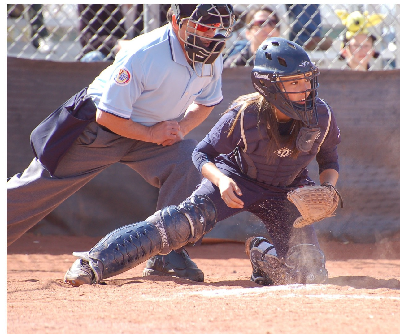 Photo of softball catcher kneeling at home plate